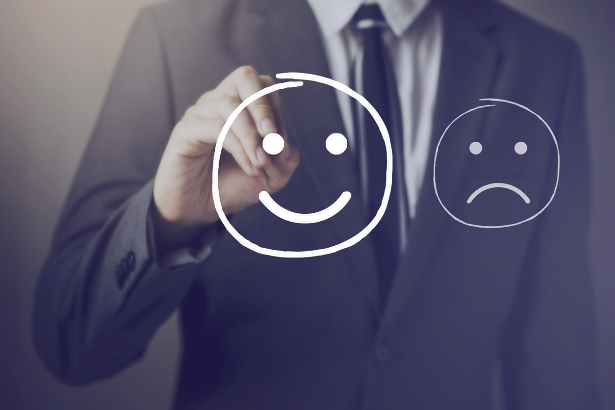 Man painting a smiley face next to a sad face