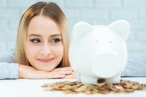 Young blond woman in front of a piggy bank